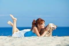 Pares novos no lado de mar que joga com seu cão Foto de Stock Royalty Free
