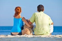Pares novos no lado de mar que joga com seu cão Foto de Stock