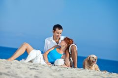 Pares novos no lado de mar que joga com seu cão Imagens de Stock