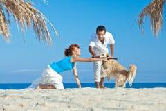 Pares novos no lado de mar que joga com seu cão Imagens de Stock Royalty Free