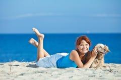 Pares novos no lado de mar que joga com seu cão Fotografia de Stock Royalty Free