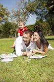 Pares novos no parque com criança Imagens de Stock Royalty Free