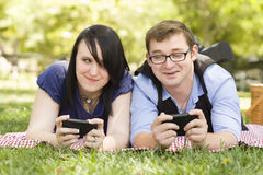 Pares novos no parque que Texting junto Imagens de Stock Royalty Free