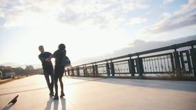 Pares novos no passeio da cidade, no abraço do homem e na amiga da rotação no por do sol, lento-movimento filme
