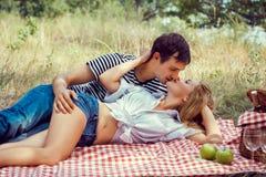 Pares novos no piquenique. abraço e beijo de encontro. Fotos de Stock Royalty Free
