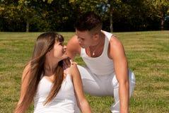 Pares novos no relacionamento branco do amor da grama Fotos de Stock Royalty Free