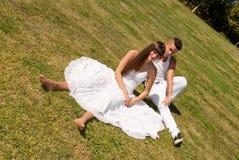 Pares novos no relacionamento branco do amor da grama fotografia de stock royalty free