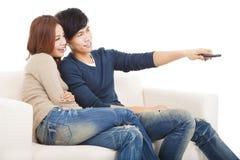 Pares novos no sofá que olha a tevê com controlo a distância Imagem de Stock