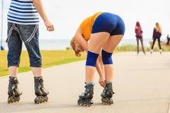 Pares novos nos patins de rolo que montam fora fotografia de stock