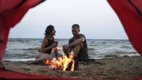 Pares novos - o homem e a mulher passam o tempo junto na praia perto do fogo, bebendo para os copos plactic vermelhos footage filme