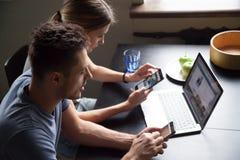 Pares novos obcecados com os smartphones e o portátil que verificam o onlin fotos de stock royalty free