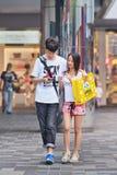 Pares novos ocupados com um telefone esperto, Pequim, China Fotografia de Stock Royalty Free