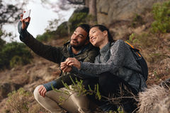 Pares novos para fora na caminhada nas montanhas que tomam o selfie fotos de stock