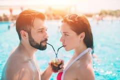 Pares novos pela piscina Homem e mulheres que bebem cocktail na água imagem de stock
