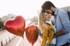 Pares novos que abraçam datar e beijar exterior imagens de stock