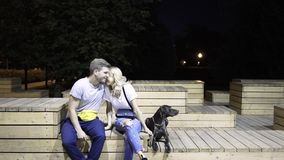 Pares novos que abraçam e que beijam Seu cão está perto deles Um parque da noite vídeos de arquivo