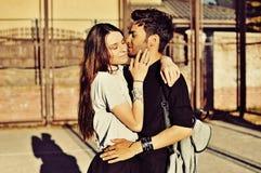 Pares novos que abraçam e que beijam exteriores Imagem de Stock