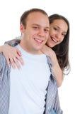Pares novos que abraçam e que sorriem Fotografia de Stock Royalty Free