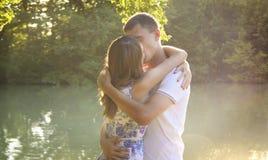 Pares novos que abraçam em um banco do rio Imagens de Stock Royalty Free