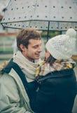 Pares novos que abraçam fora sob o guarda-chuva dentro Imagens de Stock