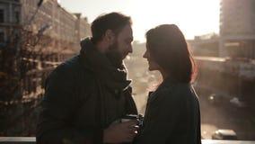 Pares novos que abraçam maciamente em uma ponte da cidade vídeos de arquivo