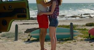 Pares novos que abraçam na praia em um dia ensolarado 4k video estoque
