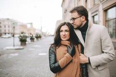 Pares novos que abraçam na rua da cidade no inverno Imagens de Stock Royalty Free