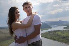 Pares novos que abraçam nas montanhas Fotografia de Stock