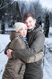 Pares novos que abraçam no tempo do inverno imagem de stock royalty free