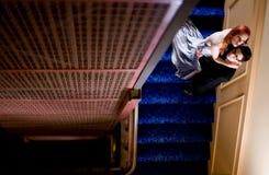 Pares novos que abraçam no vão das escadas Foto de Stock