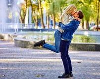 Pares novos que abraçam e que beijam no parque Fotografia de Stock