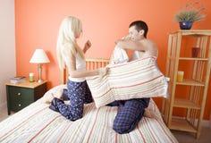 Pares novos que ajoelham-se na cama que tem uma luta de descanso fotografia de stock