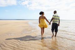Pares novos que andam ao longo da terra arrendada H da linha costeira Fotografia de Stock Royalty Free