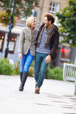 Pares novos que andam através do parque da cidade junto Imagem de Stock
