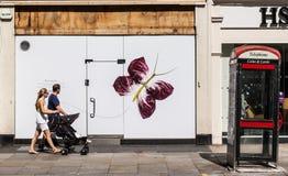 Pares novos que andam com um pram na frente de uma parede decorada com uma borboleta grande Imagens de Stock