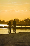 Pares novos que andam na praia no por do sol Fotografia de Stock Royalty Free