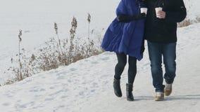 Pares novos que andam no banco do rio congelado no inverno nevado fora filme
