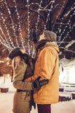 Pares novos que andam no centro da cidade do inverno sob a iluminação do feriado imagem de stock royalty free