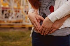 Pares novos que andam no parque que guarda as mãos Imagens de Stock