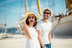 Pares novos que andam pelo porto de um recurso tur?stico do mar com os veleiros no fundo imagens de stock royalty free
