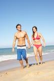Pares novos que apreciam o feriado da praia Imagens de Stock