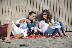 Pares novos que apreciam o piquenique na praia Fotografia de Stock