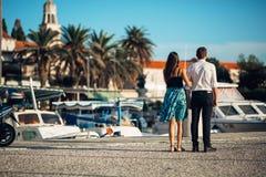 Pares novos que apreciam o tempo de férias Noivo e amiga que têm uma caminhada romântica ao longo da costa dentro uma cidade do b foto de stock royalty free