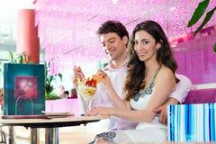 Pares novos que apreciam o tempo na sala de estar de gelado Fotografia de Stock Royalty Free