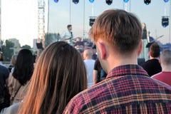 Pares novos que apreciam um concerto em uma noite ensolarada do ver?o imagens de stock royalty free