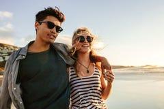 Pares novos que apreciam um dia de verão no litoral imagens de stock