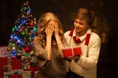 Pares novos que apresentam o presente do Natal Fotos de Stock Royalty Free