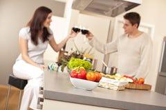 Pares novos que bebem o vinho vermelho na cozinha Fotos de Stock Royalty Free