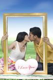Pares novos que beijam com um frame Foto de Stock