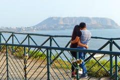 Pares novos que beijam na frente da vista pacífica, Lima, Peru imagens de stock